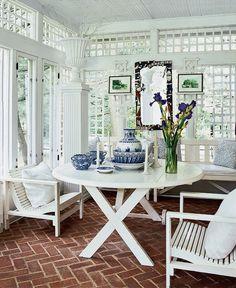 """Дом в Массачусетсе. Простые и в то же время изысканные трельяжные веранды. Изготовление трельяжа – очень кропотливая работа: чем сложнее рисунок, тем больше требуется времени и тем дороже трельяж. Здесь рисунок довольно простой, все стены и двери окрашены в белый цвет – на фоне зелени узор """"проступает"""". Правильно и то, что вся мебель также белая: надо думать, на такой веранде прохладно в самую сильную жару. Единственное цветное пятно – пол, выложенный клинкерным кирпичом: классический прием."""