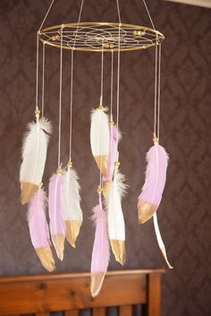 This dreamcatcher baby girl mobile is amazing. It would look awesome above your bed on somewhere to show off as a statement piece. This beautiful boho mobile made on a sturdy gold metal hoop with diameter of your choosing: 8 hoop or 10 hoop. Webbed with white cotton thread and a few gold crystal beads. There are large gold dipped snow white and light pink goose feathers are attached by gold pony beads. The size of feathers about 5-7 inches. The feathers on this mobile are so lovely and the…