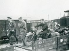 A rider with his BMW R12 prepares to disembark his machine from a military ordinance train.