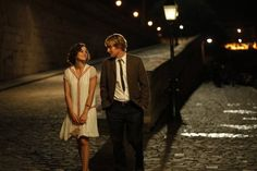 Midnight in Paris is beyond romantic!  and the dress and little purse that she is carrying!