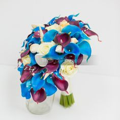"""Caribbean Callas"" real touch calla lilies bouquet in plum and turquoise, ivory roses, seashells, and pearl sprays  This unique take on our cascading callas bouquet is full of hidden treasures! Bold colors that don't overpower, and delicately added seashells to add a beach feel. This distinctive, cascading wedding bouquet is made with an abundance of the signature wedding flower – calla lily – and mixed with real touch roses, responsibly foraged seashells and pearls for the perfect…"