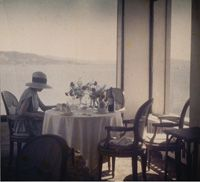 Bibi in the New Eden Roc Restaurant, Cap d'Antibes, Jacques Henri Lartigue, French, 1894 - 1986, dye coupler print > gift of rosemary speirs, Ottawa, 1996 in memory of alan john walker, Toronto, National Gallery of Canada.  portrait, single female; young woman, Bibi Messager Lartigue, wearing wide-brimmed hat seated at corner table of restaurant with windows looking across Mediterranean bay.