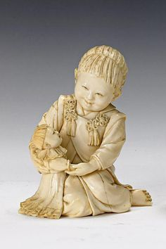 An ivory okimono of a young girl with doll by Dogyoku, Meiji period, seated with one bare foot extending to one side, her face with well defined features lowered gazing at the doll clasped in both hands on her lap, her long fringed hair tied in a bow at the back, signed on the base Dogyoku 9 cm