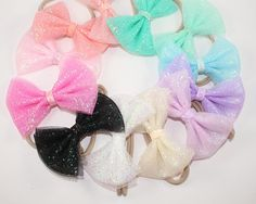 Choose one gorgeous, tulle bow headband. Perfect for Spring, Summer, and every day in between. Perfect for Newborns to Toddlers. Each bow measures approximately four inches tip to tip, and features a coordinating glitter center. Bow is securely attached to your choice of a nylon headband