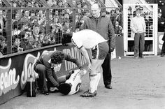 Steve Perryman looks on as Mike Varney treats an injured Chris Hughton