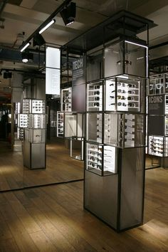 Too Many Agencies - Ray Ban Concept Store London << Interior Design - Retail Design - Eyeglasses store - Concrete columns - Greed columns - Spot lighting - Red graphic - Wooden floor - Red stools - Glazed boxes - Red accent - Illuminated shelfs >>