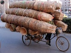 A delivery man peers out from behind the load of bamboo baskets he carries on his flat bed bicycle in a Beijing street March 12.