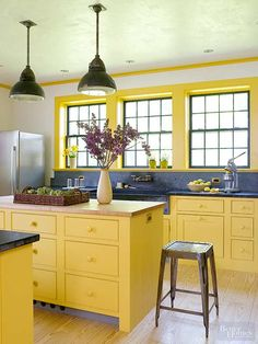 Even on a cloudy day, this farmhouse kitchen practically glows thanks to simply styled cabinets painted the color of sunshine. Pine flooring and a mix of maple and dark stone countertops enhance the room's casual tone that seamlessly blends old and new.