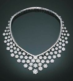 "AN ATTRACTIVE DIAMOND ""VALENCIENNES"" NECKLACE, BY VAN CLEEF & ARPELS    Designed as a knife-edge trellis-work tapered bib with circular-cut diamond florets throughout to the articulated diamond-set band, mounted in 18k white gold, 1985, 38.0 cm, with French assay mark for gold, in a Van Cleef & Arpels beige suede fitted box    Signed and with jeweller's mark for Van Cleef & Arpels, no. 134173"