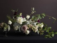 This arrangement is as sumptuous as a Dutch flower painting -- a mix of air plants, pine branches, peonies, roses and ranunculus (Styled b.