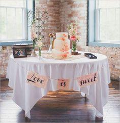 """Aqui, a toalha quadrada em uma mesa redonda tampou os pés da mesa. Um """"varalzinho"""" com uma frase escrita (aqui, """"O amor é doce"""" em inglês), dá a graça."""