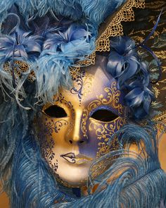 An ornate coloured Venetian face mask and feathers.
