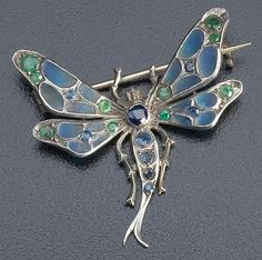 Art Nouveau dragonfly brooch in sterling with blue plique-ä-jour enamel, emeralds and sapphires.