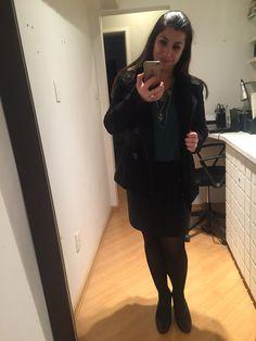 Friozão em SP pede look quentinho, mas sem perder a feminilidade: casaco de lã preto, saia lápis preta, meia calça fio 80, camisa verde escuro gola em V e colar longo de medalhas.