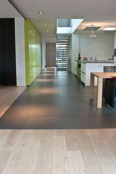 Naadloze overgang tegels naar houten vloer, gerealiseerd door MoreFloors Vloeren Breda.