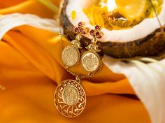 On Gudi Padva, pair the Paithani saree with a gold coin pendant and ruby studded gold coin earrings.