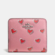 Compact yet beautifully organized, this wallet is crafted in textured leather and covered with a romantic, hand-painted heart print. The slim design snaps open to reveal an ID window and dedicated space for cards and cash.