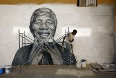 Nelson Tavares, 24, works on a mural of former South African president Nelson Mandela which he painted during festivities in his neighborhood in Lisbon, Portugal, on June 20, 2013. (Reuters/Rafael Marchante)