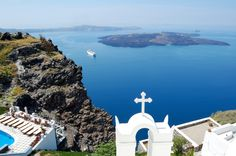 Christian Church in Santorini, Greece - Overlooking the Aegean sea and the Islands of the Cyclades. On the lower terrace the swimming pool of the hotel. Filmed during the tour of the Mediterranean world