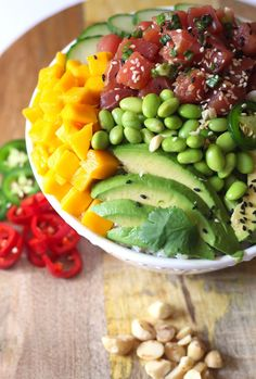 Hawaiian Style Homemade Poke Bowls are loaded with the freshest citrus ponzu flavored Ahi tuna, rice, cucumbers, avocado, edamame and mango. A drizzle of sriracha sauce and macadamia nuts for crunch are the perfect addition to this Hawaiian favorite.