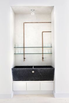 raw stone sink in a modern setting with exposed copper pipes