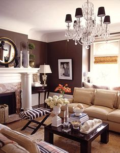 Tailored furniture and sleek white ceramic accessories against a chocolate background keep the living room current in this 1905 Edwardian San Francisco house. The crystal chandelier casts an elegant light and gives the room an air of relaxed formality. White ceramic fox is 1950s Italian. The photo of the Duke and Duchess of Windsor is by Slim Aarons.   - HouseBeautiful.com
