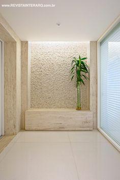 No hall de entrada, banco e molduras em mármore Travertino Romano bruto destacam a parede com mosaico em mármore rústico