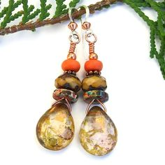 The glowing RUSTIC ALLURE handmade earrings are certainly filled with . . . well . . . allure! The one of a kind earrings feature Czech glass teardrops with a rich looking metallic Picasso finish in shades of brass and plum. Colorful, hand painted Mykonos pewter discs. Faceted tan Czech glass rondelles, copper daisy spacers and tangerine magnesite were stacked above the teardrops for perfect complements. @shadow