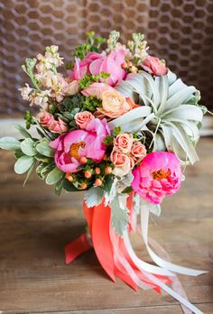 Bright pink peonies, Annabelle roses, stock, and air plants are delightfully non-traditional