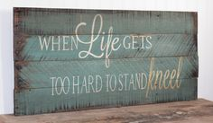 When life gets too hard to stand Kneel quote on reclaimed pallet wood board. Item measures 30 x 16. The background is weathered jade. Lettering is in