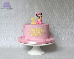 Baby Minnie Mouse cake with matching cupcakes for 1st birthday.