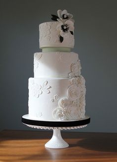 Lisette by Charm City Cakes - Classic black and white three tier wedding cake. First and second tiers separated by thin mint green colored layer. Floral gumpaste decorations adorn the entire cake with two black and white flowers on the top tier.