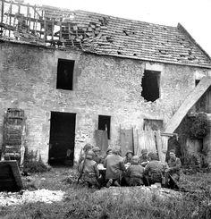 4 July 1944. Carpiquet, France. Members of the Cameron Highlanders of Ottawa  having breakfast in a barnyard during battle