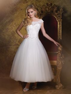 James Clifford Collection - J11590 - Wedding Dresses 2015 Collection – Hand-beaded corded lace appliqué and sequin tulle over satin tea-length full A-line wedding dress with illusion and lace cap sleeves, illusion and lace wide scooped modified bateau neckline over a beaded lace sweetheart bodice accented with Swarovski crystals and a scalloped dropped waistline, illusion and beaded lace plunging deep V-back bodice finished with covered buttons, softly gathered sequined full tulle…