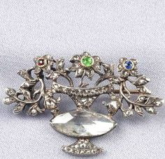 """Antique Rose-cut Diamond and Gem-set """"Giardinetto"""" Brooch, 18th century, designed as a flowerpot with navette-shape diamond measuring approx. 15.00 x 6.00 mm, and set throughout with rose-cut diamonds, each flower blossom centering a circular-cut ruby, demantoid garnet, or sapphire, silver and gold mount, lg. 1 1/2 in."""