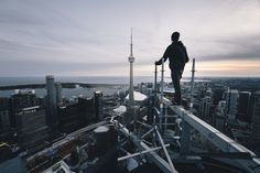 A photo of my friend standing out on the scaffolding on top of Toronto-Dominion Tower, looking out into the city.