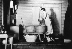 A woman, preparing to do laundry, is seen pouring water in a wash tub in this black and white photograph taken during the Depression Era.