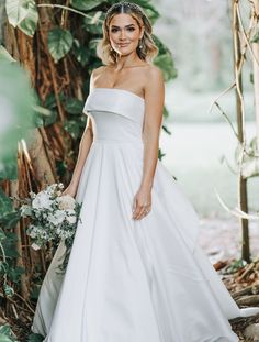 Princess Bride, Cool Girl Vibe. The Eliza Gown is a modern take on the classic off-the-shoulder neckline with a romantic circle cut ball gown skirt. In our soft & elegant Luxe Taffeta, this unique bodice has a convertible neckline that can be worn over the shoulders or tucked under the arms for a beautiful strapless look. The flirty & playful illusion cutout in the back meets princess seams on the bodice creating a flattering fit. This wedding gown is fully lined. Perfect for a winter wedding
