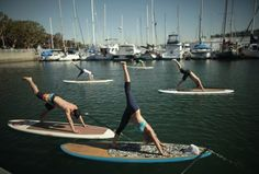 Instructor Sarah Tiefenthaler (front) demonstrates a pose during her Yogaqua class, which combines yoga and paddleboarding