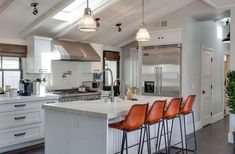 Contemporary kitchen with white cabinetry, marble island and craftsman panel door cabinets
