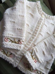 Linda chaleca color crudo para bebé con bordado en puños y guarda.