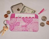 "Handmade Pink Ribbon Small Coin Purse. How cute is this? These little coin purses will surely come in handy for those days when you just need to run a quick errand. Toss it in your bag and you are ready to go. Zippered closure for added extra security along with an outside pocket and attach key ring. They are fully lined with contrast fabric color. Measures 3""x5"" fits perfect in the palm of the hands. The right size for coins, dollar bills, lip gloss, credit cards etc..."