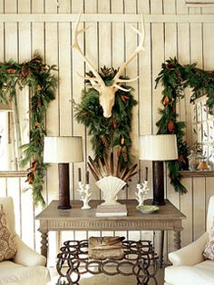 'Little Gem' magnolia leaves, long leaf pine, and pine cones adorn a pair of mirrors flanking basswood deer antlers in this sitting room.