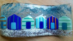 These happy beach huts in blues and subtle greens are handcut by me and fused in my kiln. I dont often do beach scenes because I feel others do it so well but I really enjoyed this. Ive used copper oxide to create lots of lovely blue bubbles behind the beach huts. The glass has been