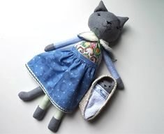 This cat doll is named Mirabelle.  She is a one of a kind, handmade doll and she has a kitten that likes to sleep in her Moses basket.Mirabelle measures approximately 46 cm (18 inches) tall from tip of her ears to toes.She wears a pretty blue skirt and a reversible wrap/shawl. Her front bodice is made from up-cycled vintage embroidered fabric. The kitten is approximately 15 cm or 6 inch tall. It has lace trim decoration and  comes with a Moses basket and blanket.Mirabelle ...