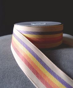 """Rainbow ribbon featuring elegant stripes in vintage style cloth. This is a not a burlap product but a popular alternative for those seeking a rustic look but without the jute fibres. 1.5"""" wide x 10 yards in length."""