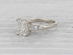 Vintage Art Deco engagement ring made in platinum and centered with a GIA certified 1.91 carat I color VS2 clarity emerald cut diamond. Accented with six french cut diamonds. Circa 1925. French cuts a