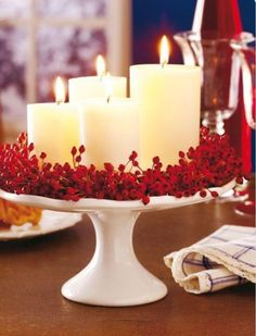 White Lit Candles surrounded by Red Flowers on a Cake Stand.