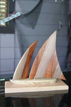 Wooden Sailboat - The jib (front sail) can swing back and forth allowing you to adjust how you want it to look when on your tabletop. Each piece of wood has its own unique appearance and varies slightly so each sailboat will be unique.  This makes a great gift for many occasions including Birthdays, Father's Day, 5 Year Anniversary, or for yourself. Sailboat Lovers, Sailboat Collectors, or Nautical Lovers of all ages will love it. http://woodsmithofnaples.com/wooden_sailboat_6.html