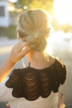Pulled back bun. Twisted sides. cute shirt.